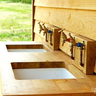 Innovative and practical washroom cabin on campsite showcasing natural materials and rustic charm.  Life Space Cabins
