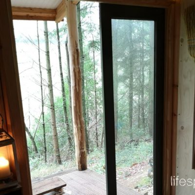 Woodland Foresters Cabin looking outward with candles giving a cosy hygge space in Devon |Life Space Cabins